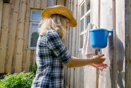 farmer cowgirl woman wash hands under rural plastic hand washer tool water.  photo