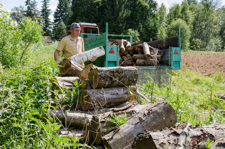 Lumberjack worker man load tree logs for firewood in tractor trailer.  photo