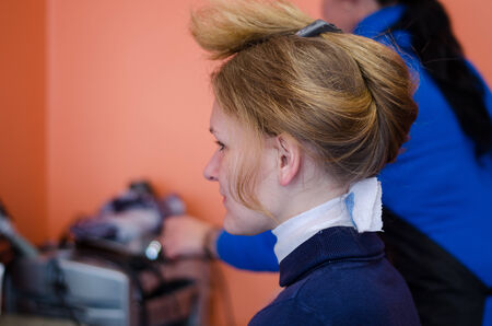 young blonde woman in chair at the beauty salon hairdressers