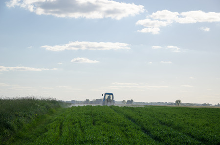 metering: Tractor spray field with chemicals and man with metering tool in agriculture field and evening sunlight.