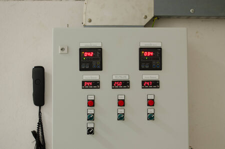 control panel lights: Switches buttons lights and phone on industrial control panel board.  Stock Photo