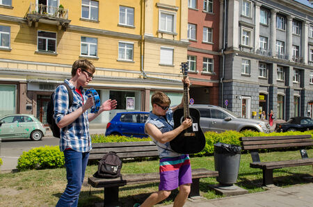 VILNIUS, LITHUANIA - MAY 18: cheerful active buskers with guitars and bell on city street on May 18, 2013 in Vilnius.