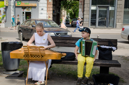 VILNIUS, LITHUANIA - MAY 18: young street music festival participants girl with baltic psaltery and boy with accordion on the bench on May 18, 2013 in Vilnius.