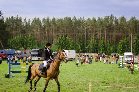 steeplechase: NIURONYS, LITHUANIA - JUNE 01: woman ride horse in horserace steeplechase competition on June 01, 2013 in Niuronys, Lithuania.