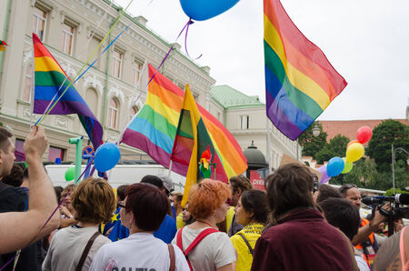 marchers: VILNIUS, LITHUANIA - JULY 27: colorfully dressed gay lesbian marchers holding flags balloons chanting slogans on July 27, 2013 in Vilnius.