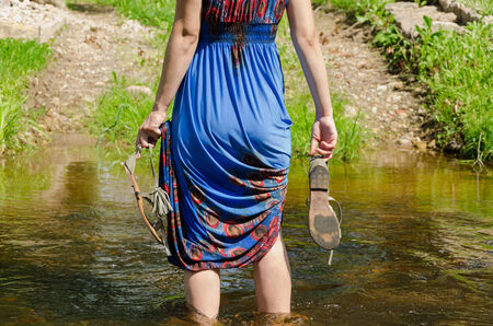 wade: girl holds gray summer sandals and wade barefoot through the fast flowing stream in the park track