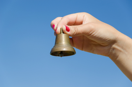 Woman hand with red nails shake small iron bell and jingle sounds on background of blue sky.