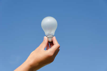 hand holding an incandescent light bulb on blue sky background  photo