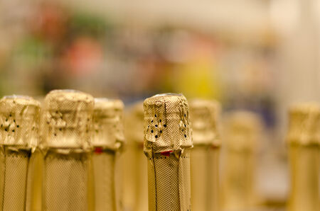 cloesup: close up of champagne bottleneck cork wrapped yellow shiny paper