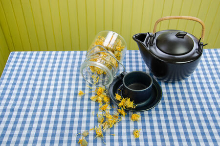 jar with dried ecology coltsfoot on table and vintage black ceramic tea pot  photo
