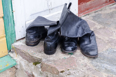 ratty: old black leather men high shoes on the cement surface outdoor