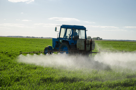 Tractor spray fertilize field with insecticide herbicide chemicals in agriculture field and evening sunlight.   photo