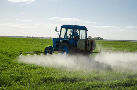 Trekker spuiten bemesten veld met insecticide herbicide chemicaliën in de landbouw gebied en avond zonlicht. Stockfoto