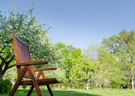 brown wooden garden chair outdoors on spring garden tree background