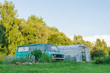 old mini bus parked next to the village greenhouse in the yard  Stock Photo