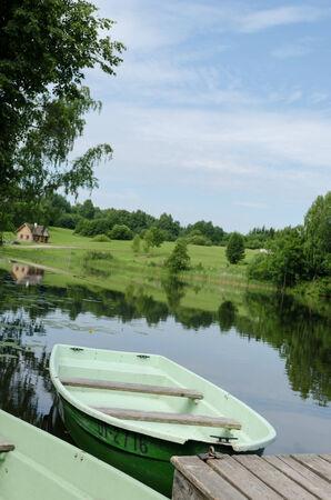 green boat: green boat moored to wooden footbridge at lake shore