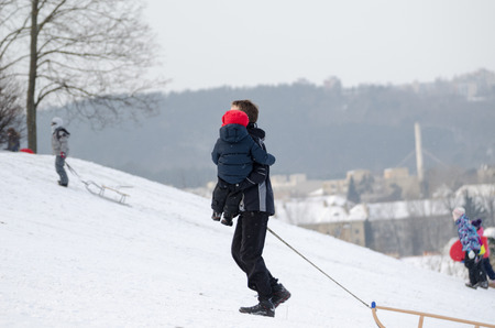 father with child climb up the snowy hill in nice winter weather  photo