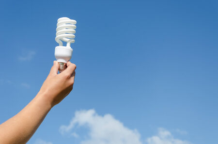 hand holding energy saving lamp on blue sky background  photo