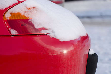 red car front lamp covered with powdery snow in cold winter weather