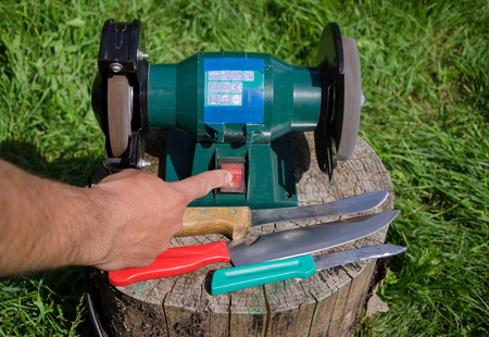 sharpening process: man finger push electric knives steel button on stump outdoor