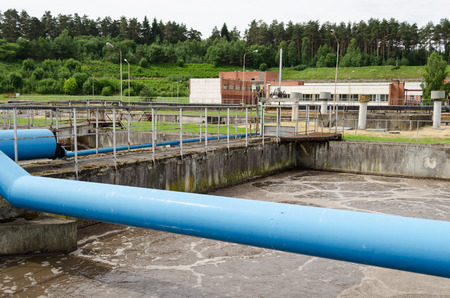 sludge: wastewater sewage water aeration basin bubbling and big pipes blowing oxygen. Polluted water cleaning technology. Modern treatment cleaning plant.  Stock Photo