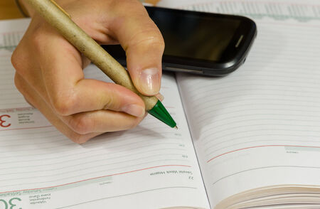 Business woman hand with pen make write notes in notebook and mobile smart phone.  photo