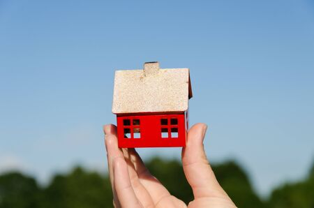 woman hand hold small metallic house miniature on blue sky background