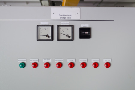 Sludge sieve control panel board with meters and red green lights in water treatment plant.  photo