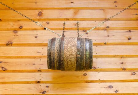 gable house: gable of the wooden rural house and decorative barrel with chains  Stock Photo