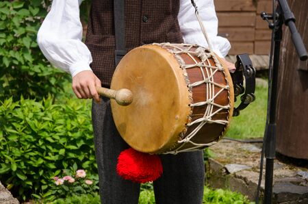 Drummer play folk music with drum and stick in rural village party.  Stock Photo