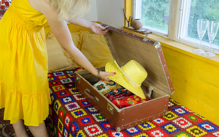 woman with yellow summer dress put straw hat in old leather suitcase   Stock Photo
