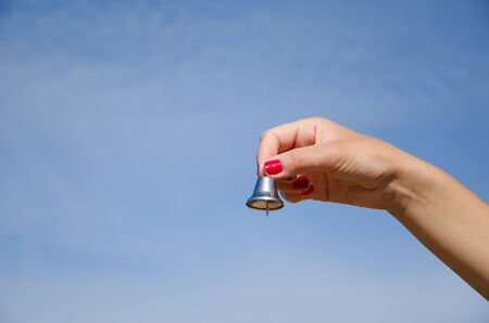 hand with red nails shake small silver bell and jingle sound on background of blue sky.