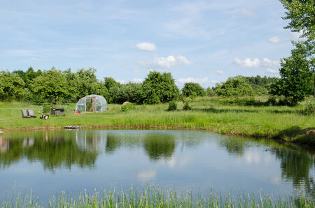 village big pond and greenhouse in summer nature  Stock Photo