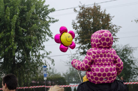 little girl with pink dotted jacket and flower shape balloon sit on dad shoulders