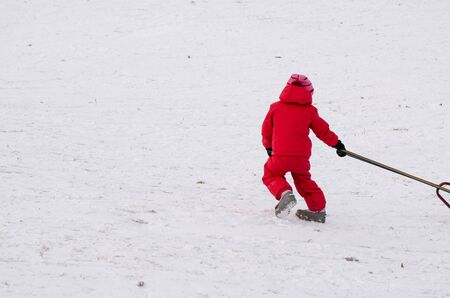 child with red waterproof overall in snow covered field in winter time