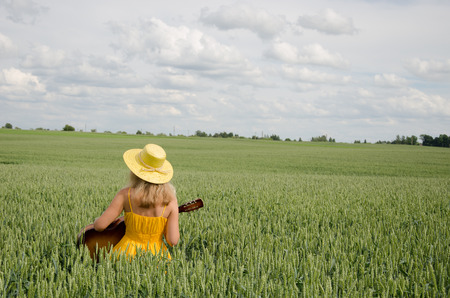 Country woman in yellow dress and hat on head play with guitar at wheat field.