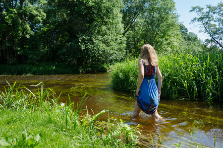 blonde girl with long blue mottled summer dress wade through fast flowing river in summer day