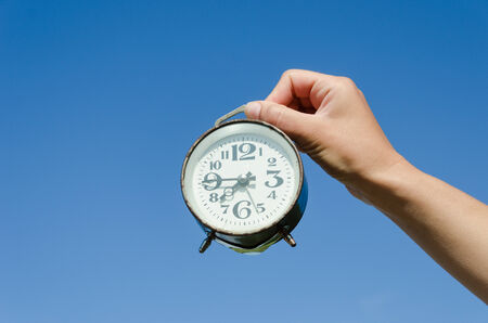 girl hand hold small old retro alarm clock with large black numerals on blue sky background