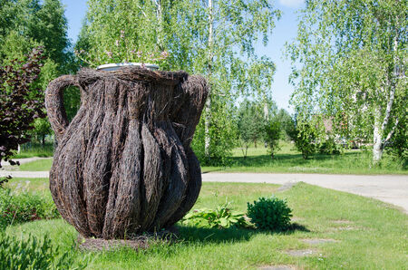 weaved: dekorative big pitcher weaved from dried birch branches in village outdoor  Stock Photo
