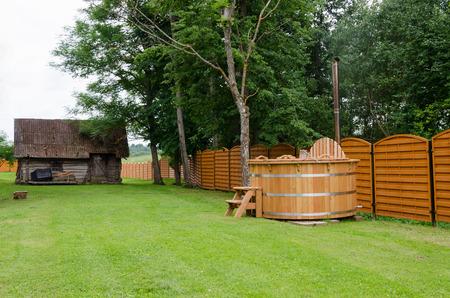 new modern wooden hot tub of water rural yard. outdoor bathhouse pleasure.  photo