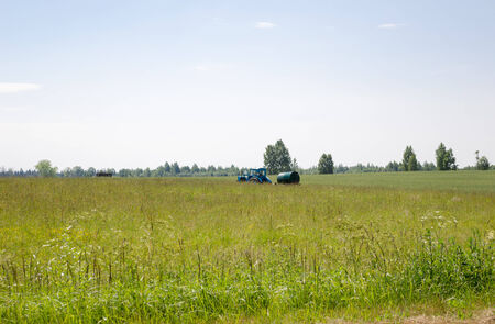 working tractor with water tank in high wide pasture meadow