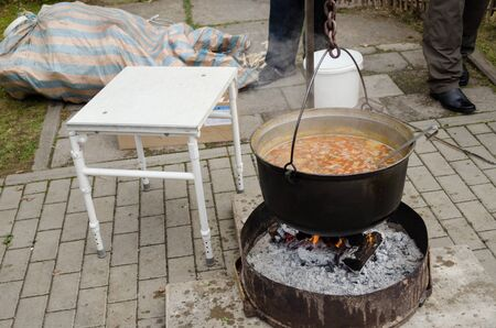big black metal old pot full of rustic vegetable soup on an open fire outdoors  Stock Photo