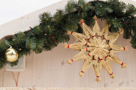 handmade christmas tree decoration star twisted from dry straw hanging on the house corner   Stock Photo