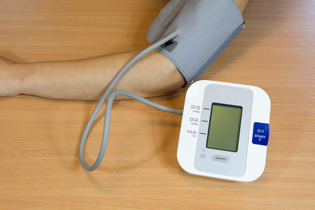 female patient checking measuring her blood pressure with special device tool.   Stock Photo
