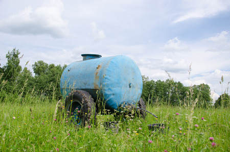 Blue water cistern for animal stand between pasture high grass and clovers move in wind.  Stock Photo