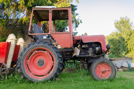 plough machine: close up of old rural tractor with red wheels in garden nature