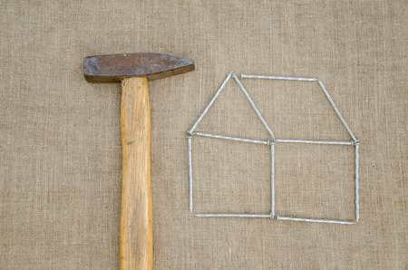 work hammer and outbuilding shape of metallic nail on linen texture background  Stock Photo