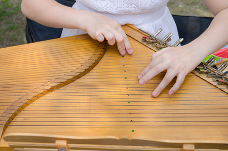 ancient wooden stringed traditional baltic psaltery and the girls hands