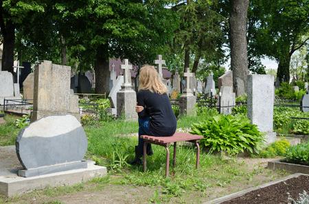 Sorrow woman shrinked near father husband tomb in graveyard.