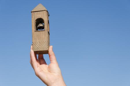 female hand hold old vintage wooden belfry miniature on blue sky background